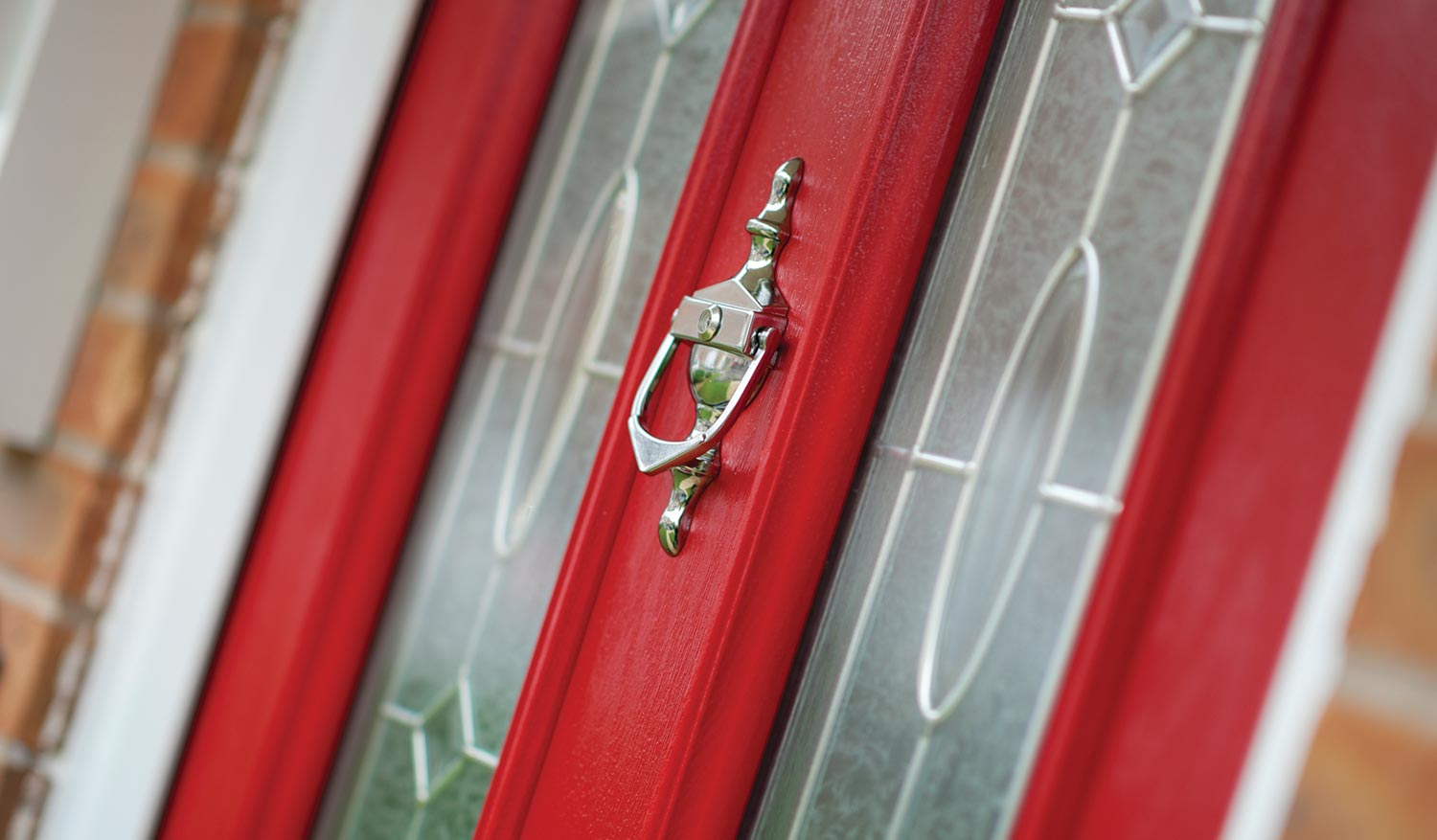 Red composite entrance door with glazed panels and chrome hardware