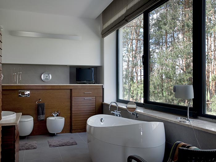 Sleek aluminium windows internal view from bathroom onto garden