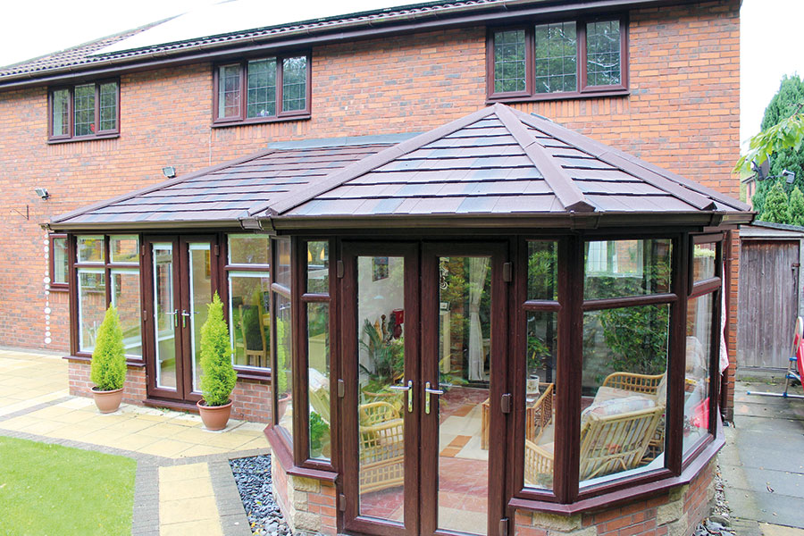 brown upvc conservatory with brickwork /></li>