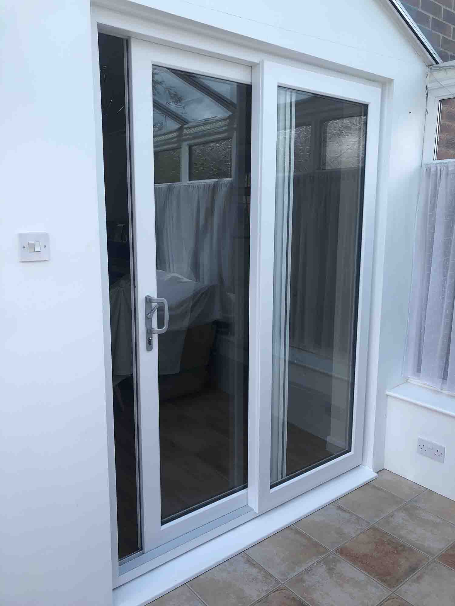A white sliding door leading to conservatory.
