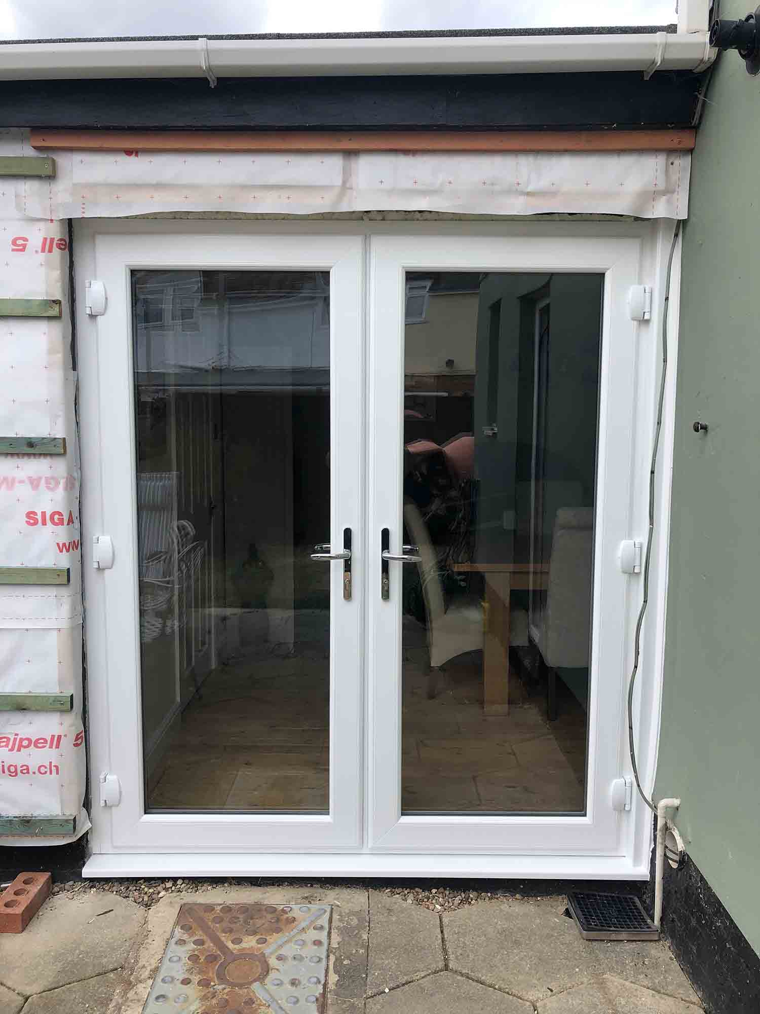 New white French door installed in new extension.