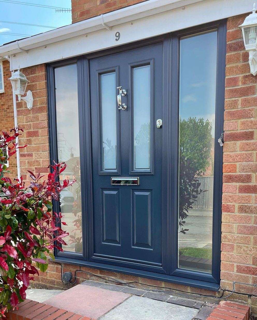 Black front door with glass side panels.